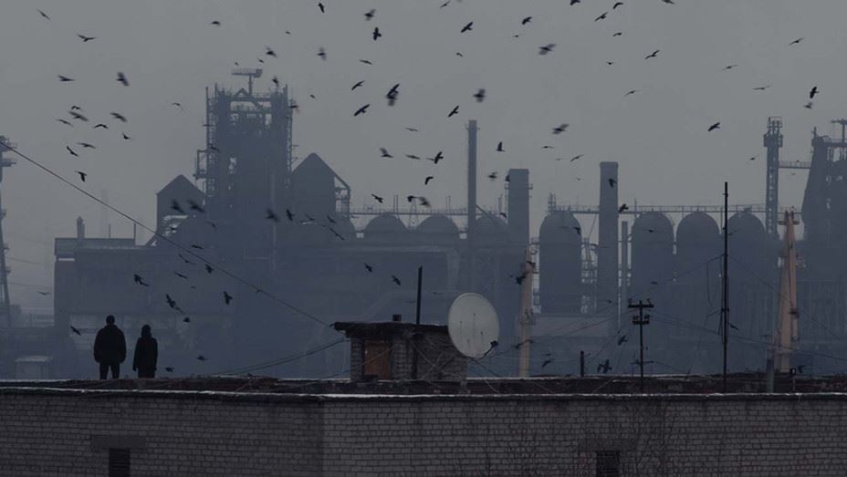 couple on roof, far away shot, birds fly over an industrial scene